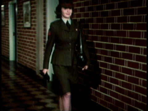 1968 MONTAGE Military recruitment video showing woman marine in well groomed and fitted uniform walking down hall and out of a building / United States