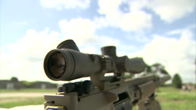 a military rifle includes a scope. - fadenkreuz stock-videos und b-roll-filmmaterial