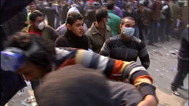 vídeos de stock, filmes e b-roll de military rulers offer to bring forward elections as violence continues in tahrir square protesters running from tear gas protesters carrying... - arab spring