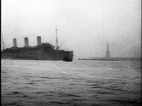 vidéos et rushes de b/w 1918 military ship sailing into ny harbor past statue of liberty after end of ww i - 1918