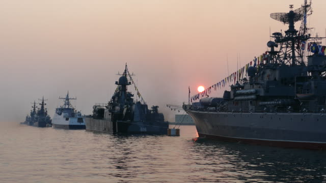 military ships in the bay at sunset