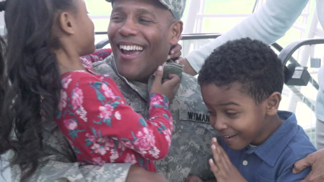 military soldier returning home greeted by his family - ホームカミング点の映像素材/bロール