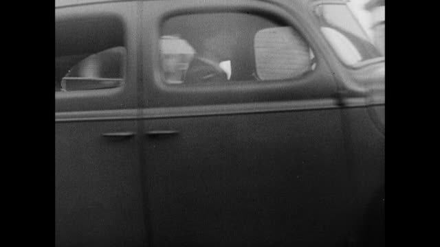 stockvideo's en b-roll-footage met b/w military staff car pulling up to inn beside forth bridge, sign for inn with train passing beyond, and officer from car crossing road and entering inn / rosyth, scotland, united kingdom - 1940