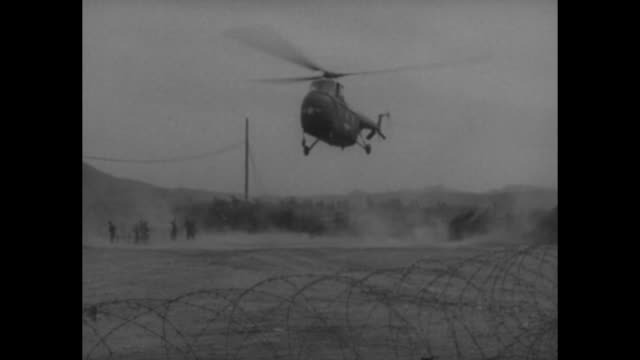 military staff member at door of justlanded usaf helicopter / helicopter lands behind razor wire barrier / jeep moves past bearing members of the un... - note pad stock-videos und b-roll-filmmaterial