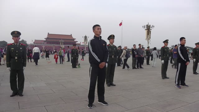 military stand at attention in tiananmen square during a national holiday in beijing. - tiananmen square stock videos & royalty-free footage