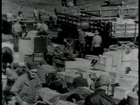 military supplies on beach w/ navy landing craft in shallow water bg. vs us allied soldiers unloading boxes & pushing artillery on beachfront - seicht stock-videos und b-roll-filmmaterial
