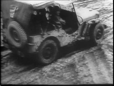 military supply trucks passing each other on muddy road / jeep driving through mud / wheels of truck driving through mud / soldiers walk through... - tail wing stock videos and b-roll footage