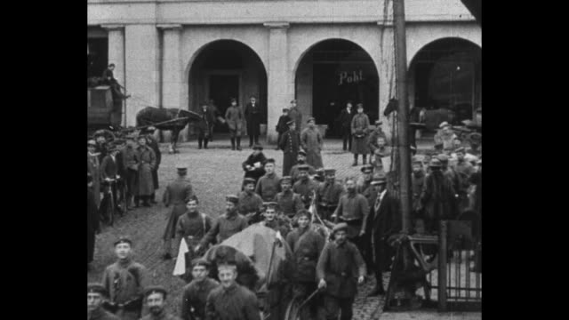 vídeos y material grabado en eventos de stock de military supply wagons proceed down a boulevard with arched towers / former crown prince wilhelm stands with german officers / soldiers with... - 1910 1919