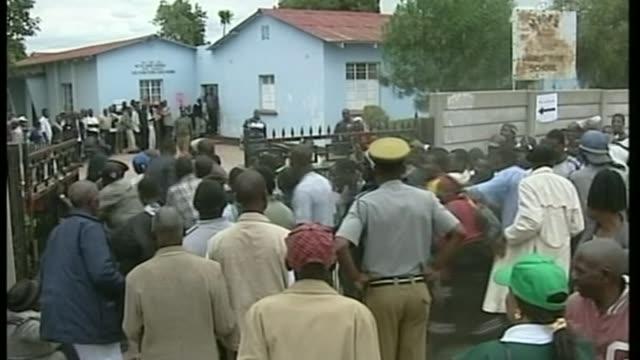 Robert Mugabe profile T09030221/ TX Crowd along through gates to polling station