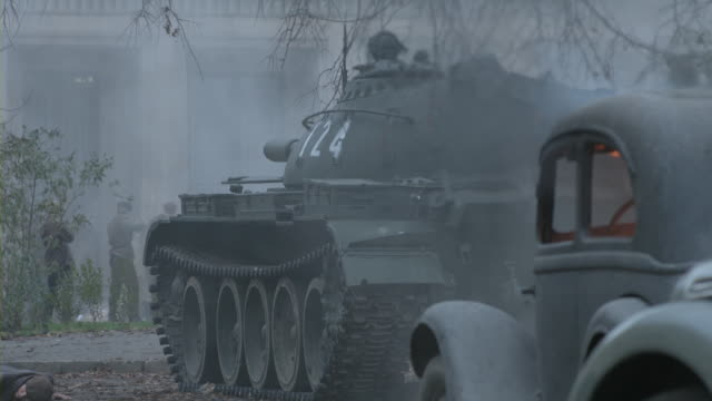 A military tank fires on a building amid smoke and fires.