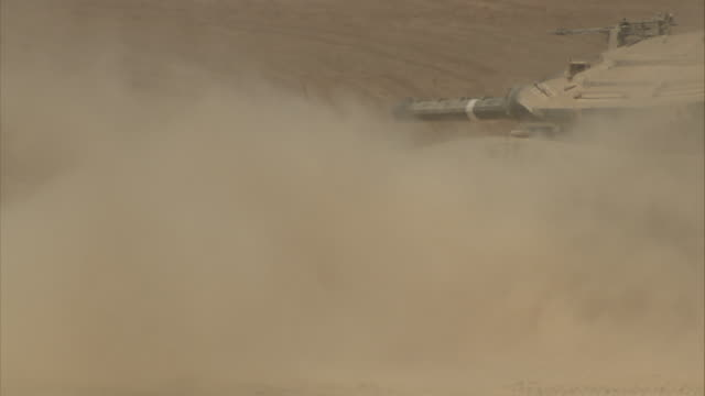 a military tank kicks up sand as it rumbles across a desert. - israel stock videos & royalty-free footage