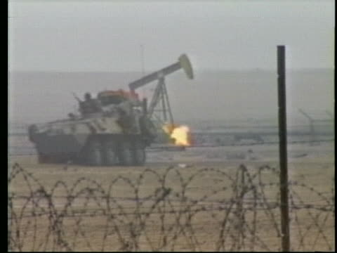military tanks drive past a burning oil well in iraq during desert storm. - iraq stock videos & royalty-free footage
