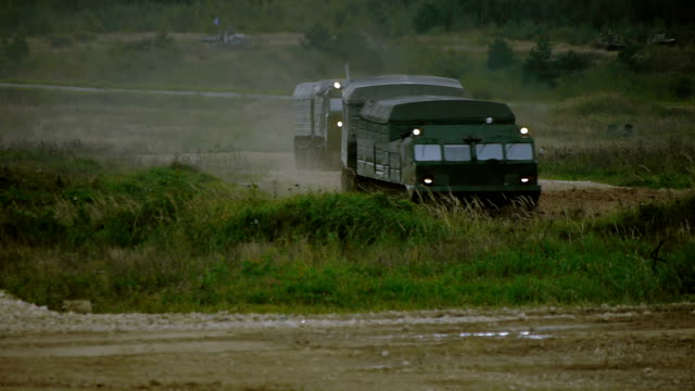 Military tracked vehicles on a dirt road