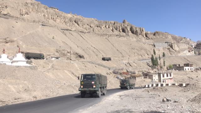 Military trucks drive on the road at Lamayuru in Leh Ladakh, Jammu and Kashmir, India