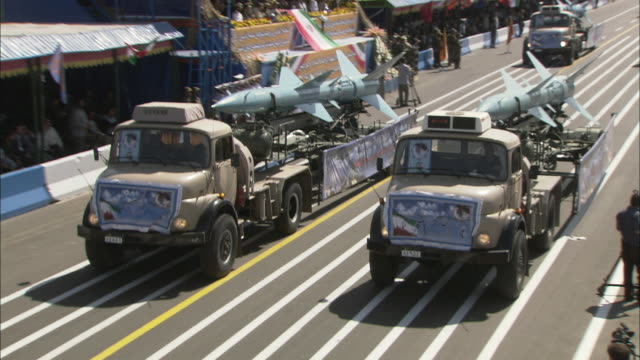 vídeos de stock, filmes e b-roll de ws zo military trucks including missile launchers passing for official parade / tehran, tehran province, iran  - irã