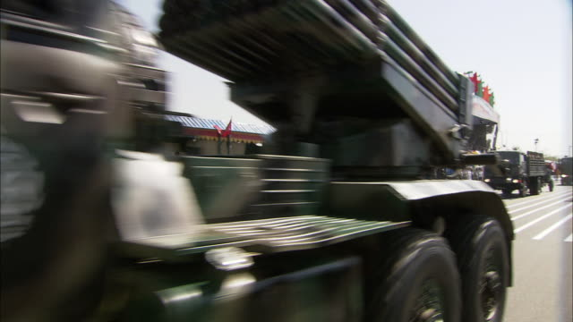 military trucks transporting heavy artillery pass slowly by a reviewing stand in a military parade. - army stock videos & royalty-free footage