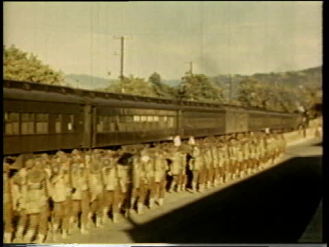 1941 ha military unit marching in line alongside a parked train / united states - bahnreisender stock-videos und b-roll-filmmaterial