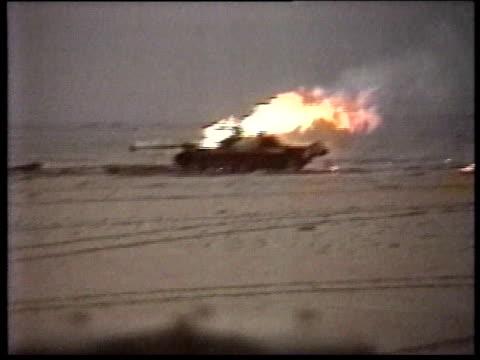 military vehicle burning in desert terrain US Army vehicle driving past it / military vehicle burning in desert terrain / military vehicle smoldering...