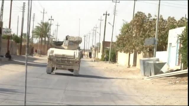 ws pov military vehicle on road in town, haditha, al anbar, iraq - iraq stock videos & royalty-free footage