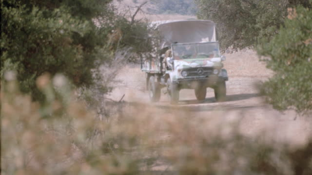 a military vehicle passes grazing zebras. - tierisches verhalten stock-videos und b-roll-filmmaterial