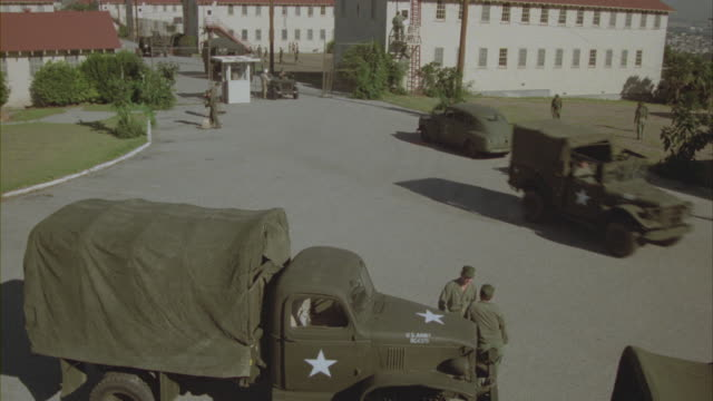 Military vehicles congregate outside a military base.