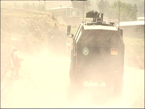 Military vehicles drive through a desert village.