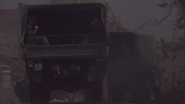 Military vehicles drive through a war zone.