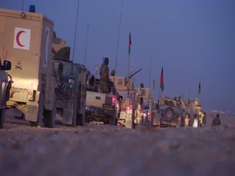 military vehicles queue in a road in afghanistan - 2001年~ アフガニスタン紛争点の映像素材/bロール