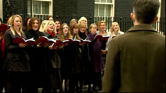 vidéos et rushes de military wives choir perform at downing street england london downing street no10 ext military wives choir singing carol outside no10 downing street... - chanteur