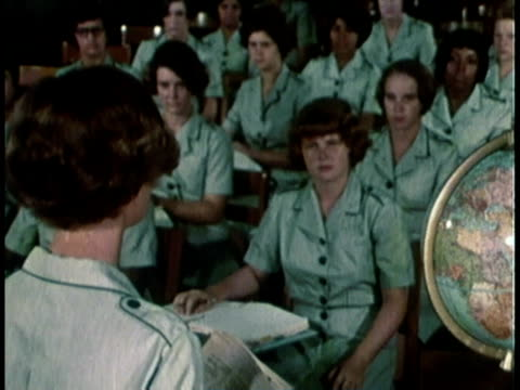 1968 montage military women sitting at desks in a classroom while teacher talks about current events / united states  - anno 1968 video stock e b–roll