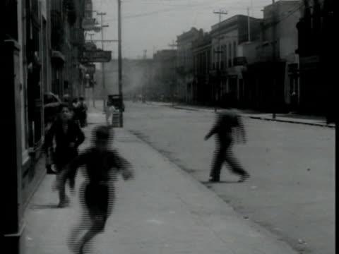 militia soldiers w/ rifles walking down street crowd on sidewalk. children running on sidewalk smoke bg. horseback policemen riding through street... - 1940 stock videos & royalty-free footage