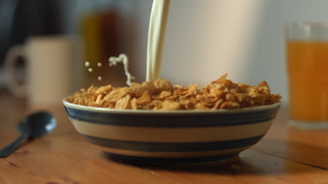 CU SLO MO Milk being poured in full of cornflakes bowl and milk splashes / Manchester, United Kingdom