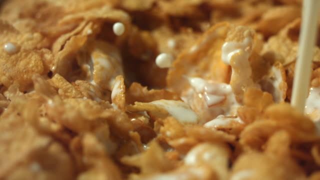 cu slo mo milk being poured into cornflakes / manchester, united kingdom - pouring milk stock videos & royalty-free footage