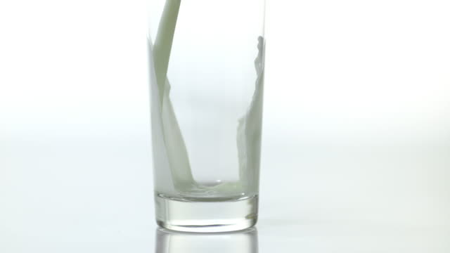 milk being poured into glass against white background, slow motion 4k - füllen stock-videos und b-roll-filmmaterial