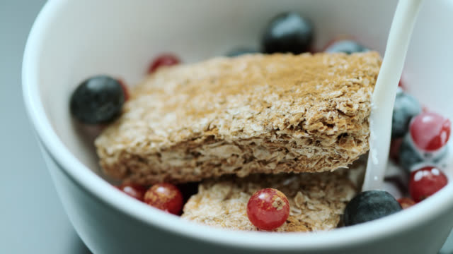 slo mo milk being poured onto oat bars with fruit - breakfast stock videos & royalty-free footage