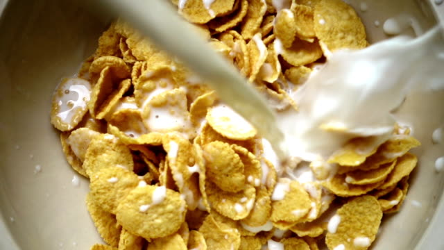 slo mo - milk being poured onto the breakfast cereal - bowl stock videos and b-roll footage