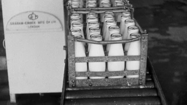 montage milk bottled in factory by workers and sent out on trucks to be delivered / united kingdom - 1943 stock videos & royalty-free footage