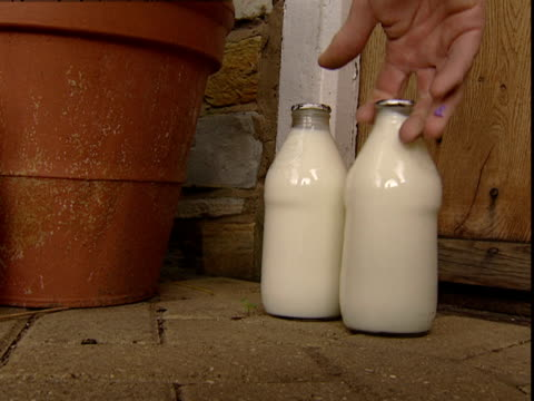 milk bottles are placed on a porch. - milkman stock videos & royalty-free footage