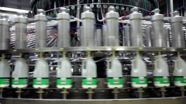 milk bottles being filled with milk by a large spiraling machine - efficiency stock videos and b-roll footage