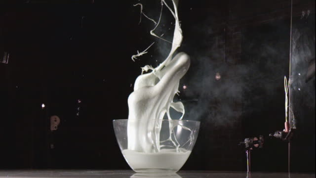 milk explodes in a glass bowl. - messy stock videos & royalty-free footage
