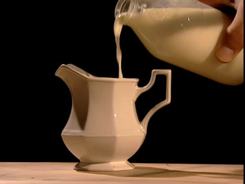 milk from a glass bottle pours into a jug. - milk jug stock videos & royalty-free footage