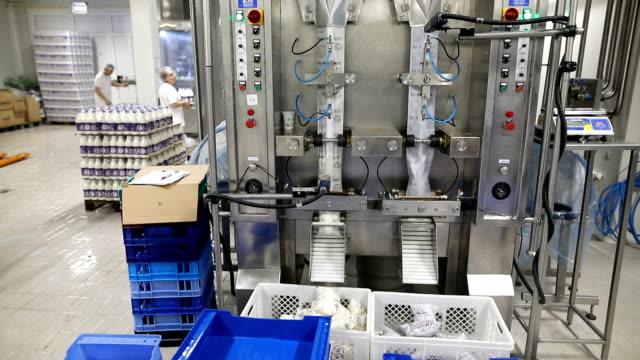 stockvideo's en b-roll-footage met melk in een plastic zak. verse zuivelproducten zakken bewegen op een transportband. - dairy product