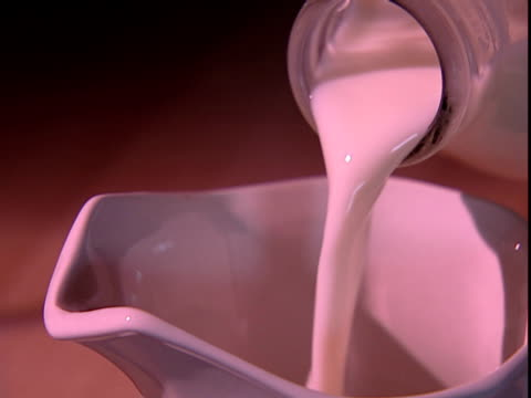 milk is poured from a glass bottle into a jug. - milk jug stock videos & royalty-free footage