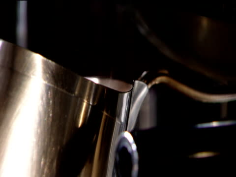 Milk is steamed in jug using steam spout of coffee machine in coffee shop