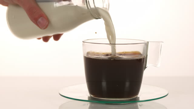 Milk poured into a Cup of Coffee against White Background, slow motion 4K