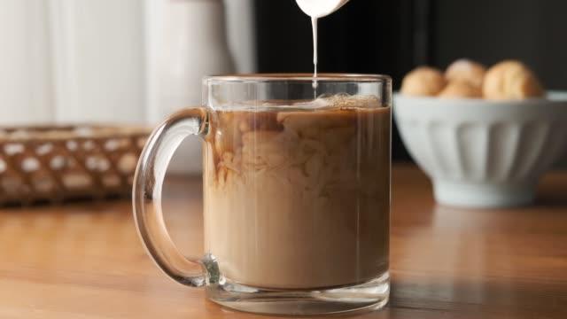 vidéos et rushes de milk pouring in black coffee - mug