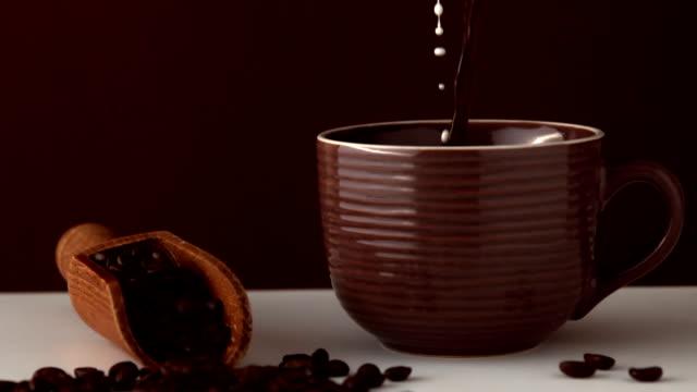 vídeos de stock, filmes e b-roll de leite que entra em marrom xícara de café - molécula de cafeína