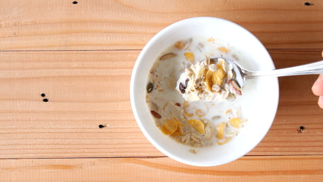 milk pouring into cereal bowl on wooden background