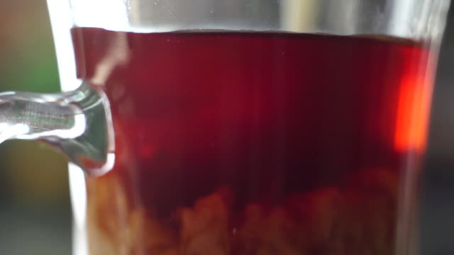 CU SLO MO milk pouring into clear mug of tea/ Johannesburg/ South Africa