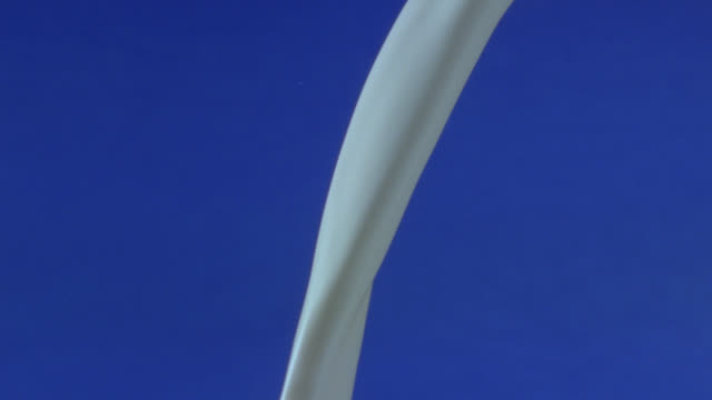 milk pours against a blue background. - liquid stock videos & royalty-free footage